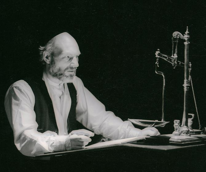Shylock in the trial scene, sat in front of an old-fashioned set of scales