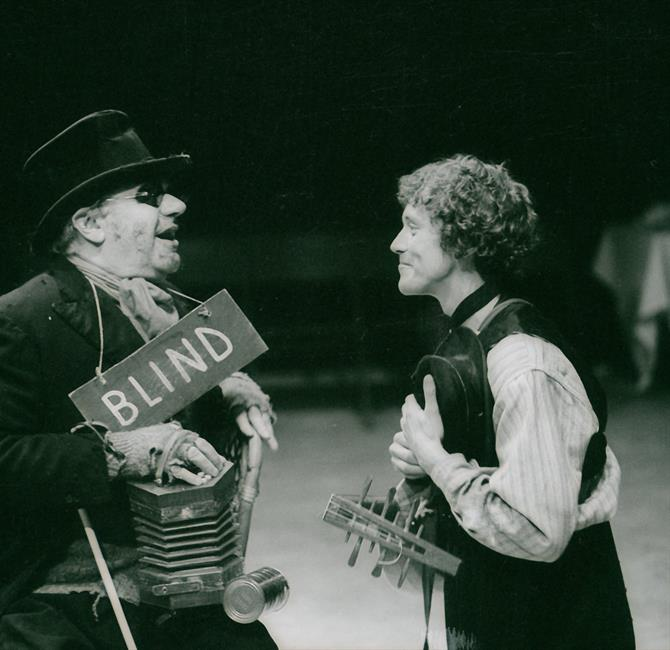 A man carrying a lute talks to an older man wearing a top hat and a wooden sign with the word 'BLIND' painted on it