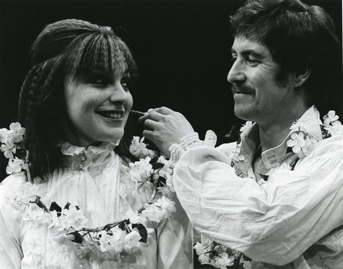 Portia and Bassanio happily reconciled, both wearing white and flower garlands