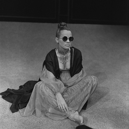 Estelle Kohler as Silvia, wearing a low-cut, flowing gown and round sunglasses