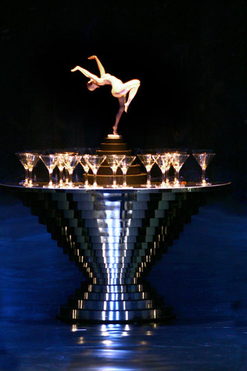 An art deco cocktail bar with a figurine of a woman dancing on top and martini glasses on the surface