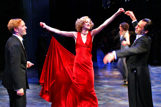 A woman in a red dress with a long train attached to her arm dances with two men in tuxedos