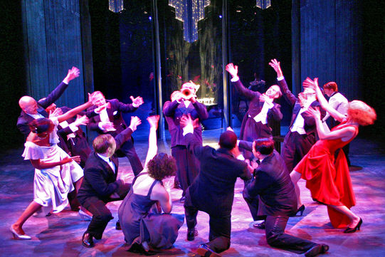 The cast on stage dancing to the music of a trumpeter