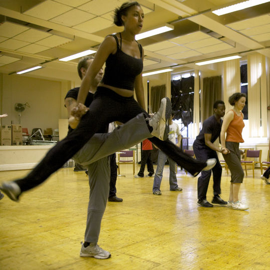 The cast rehearse the dances, with a woman leaping into the air