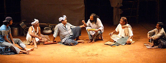 Actors sit in a row on a sandy stage