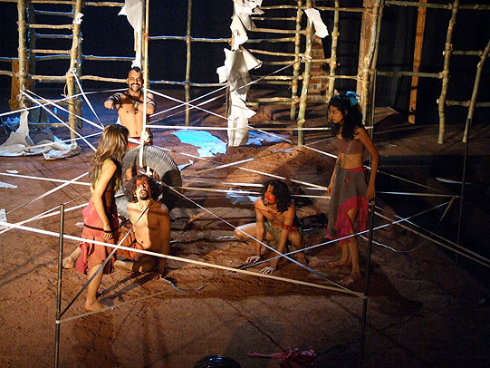 Actors on a sandy stage, surrounded by white tape stretched between them