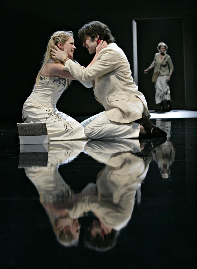 Two lovers embrace. They are reflected in the shiny black floor.