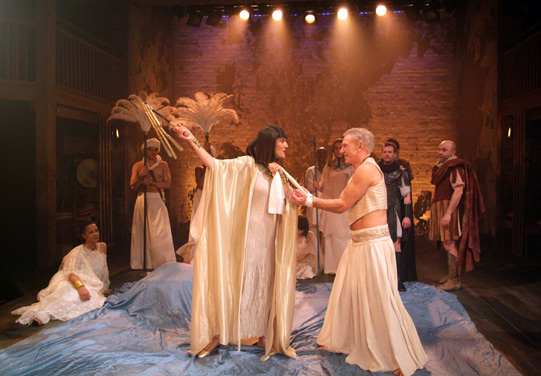 Cleopatra threatens Antony with a whip as she leads him on with his hands tied.