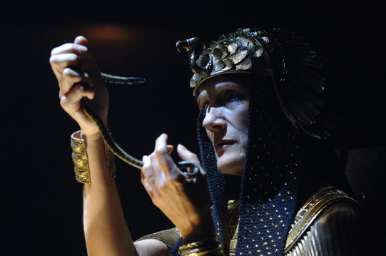 Cleopatra holds the snake to her face