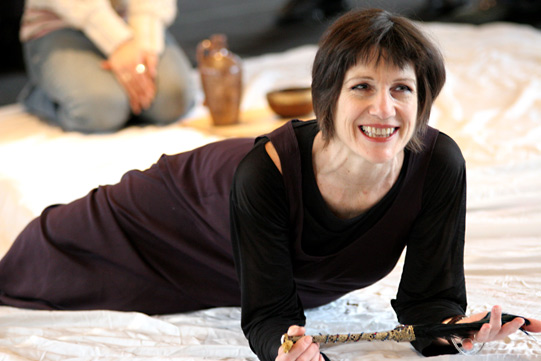 Harriet Walter in all black lying on blankets holding a bunch of black feathers in her hands