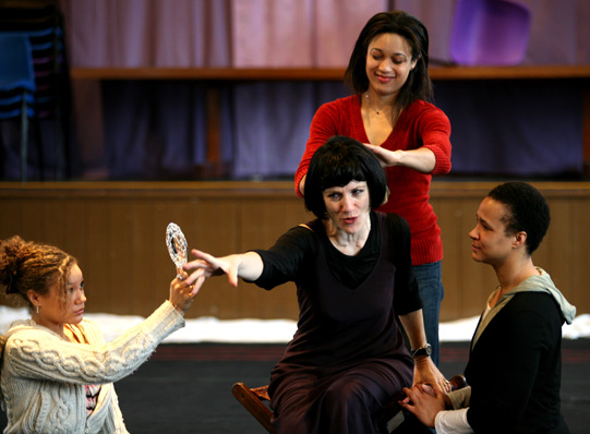 Harriet Walter rehearsing as Cleopatra, wearing all black and reaching out for a mirror her attendant is holding