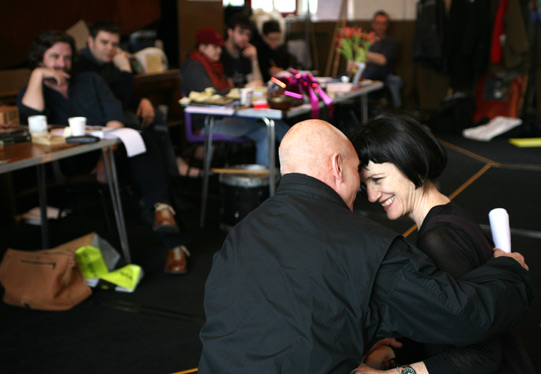 Patrick Stewart and Harriet Walter hold each other, touching foreheads and laughing, while Gregory Doran and others watch
