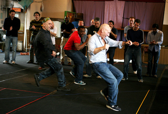 Patrick Stewart leading two others in a dance, while other men watch and clap