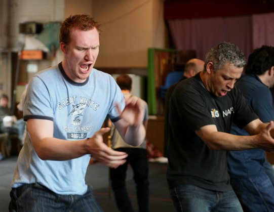 Actors in t-shirts and jeans dancing together and clapping