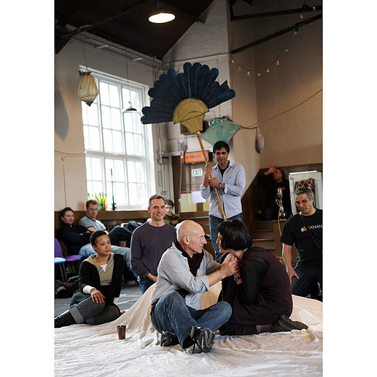 Patrick Stewart and Harriet Walter sitting together on a blanket, surrounded by attendants, one of them holding a huge decorative fan