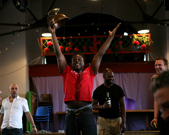 Ariyon Bakare with his arms outstretched, holding an empty bronze bowl, his body drenched in water