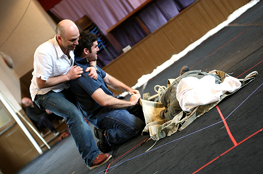Joseph Alessi and Rob Carroll, one of them kneeling in front of a pile of rags and the other holding him from behind