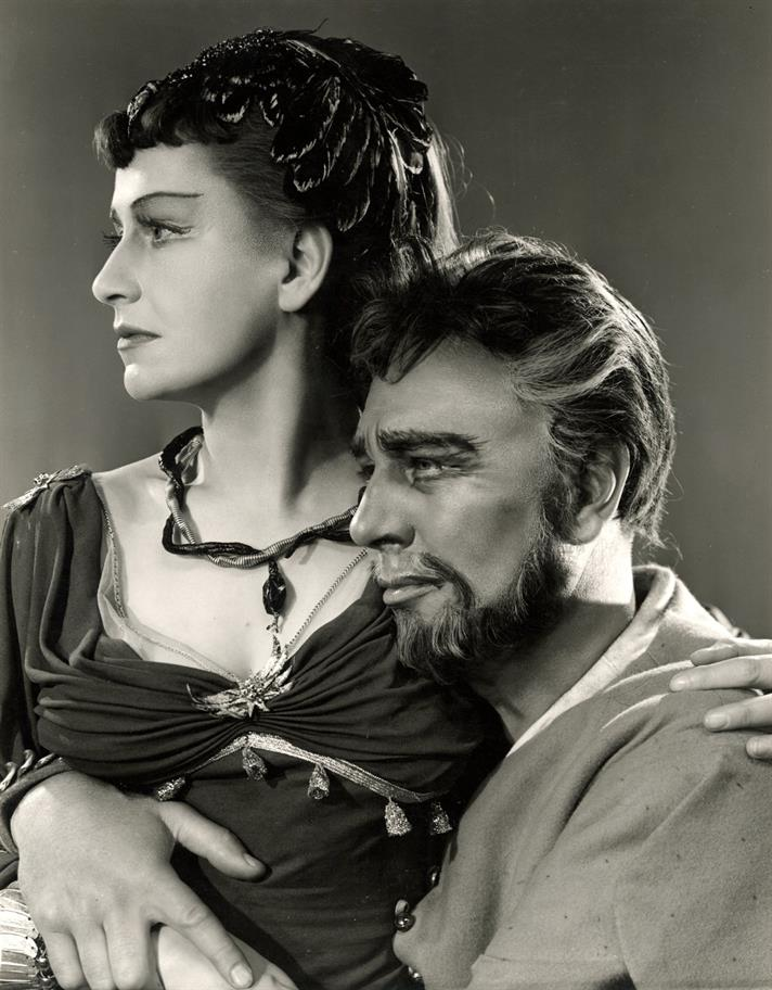 Peggy Ashcroft as Cleopatra and Michael Redgrave as Antony. Cleopatra wearing a dark dress and sitting in Antony's lap