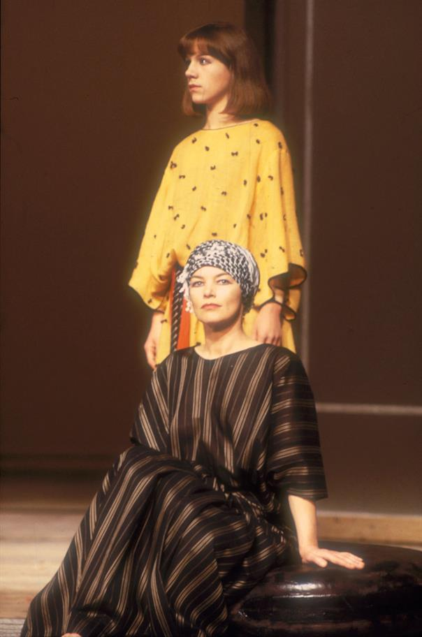 Glenda Jackson as Cleopatra and Juliet Stevenson as Iras. Iras in a long yellow robe stands over Cleopatra, who is wearing a headscarf