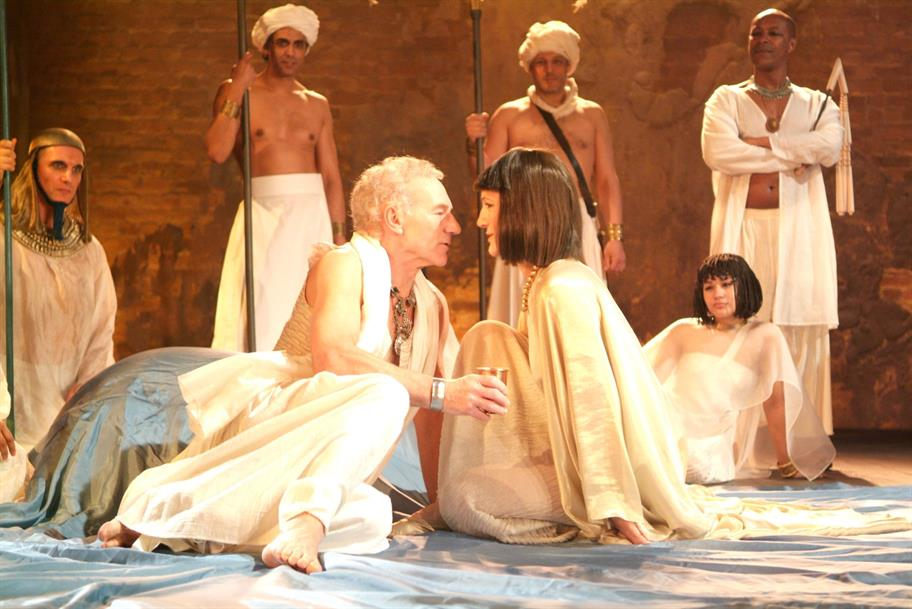Patrick Stewart as Mark Antony and Harriet Walter as Cleopatra, surrounded by guards and maids. All are wearing white