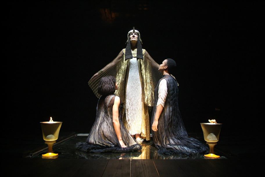 Cleopatra stands above two people in black gauze robes. Two lanterns stand lit by her side.