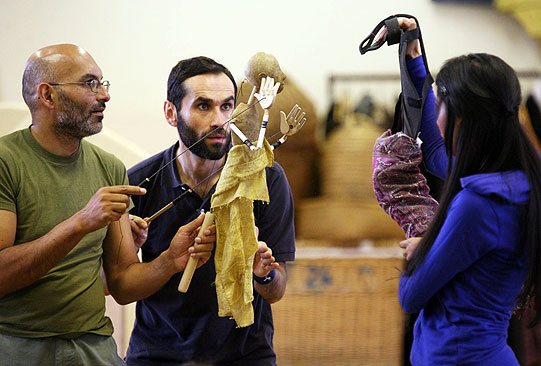 Two actors rehearse with the puppet of a man, making it interact with a woman in blue
