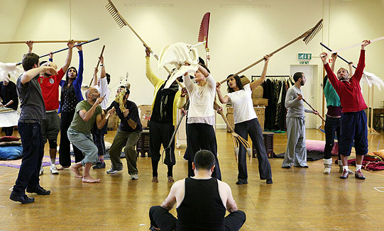 actors in rehearsal working together using a large model skull, rakes and sticks