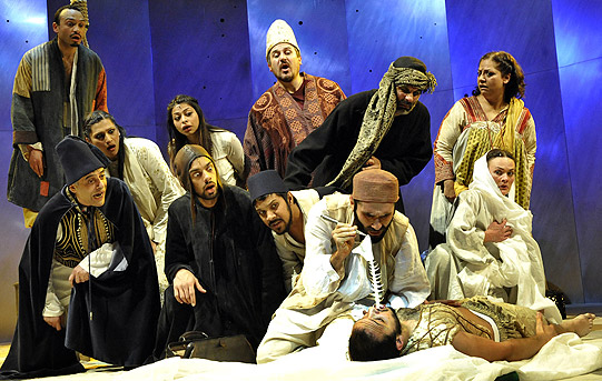 A production image showing the company of Arabian Nights on stage looking at a a motionless man on the floor