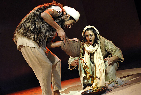 Ali Baba empties out the treasure he's found in the cave, to the amazement of his wife
