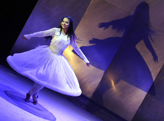 Shahrazad (Ayesha Dharker) spinning around with a wide white skirt