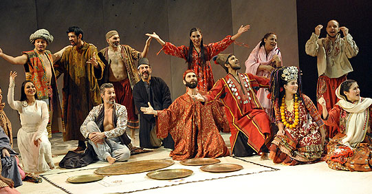 The Arabian Nights company in orange robes seated in a semi-circle