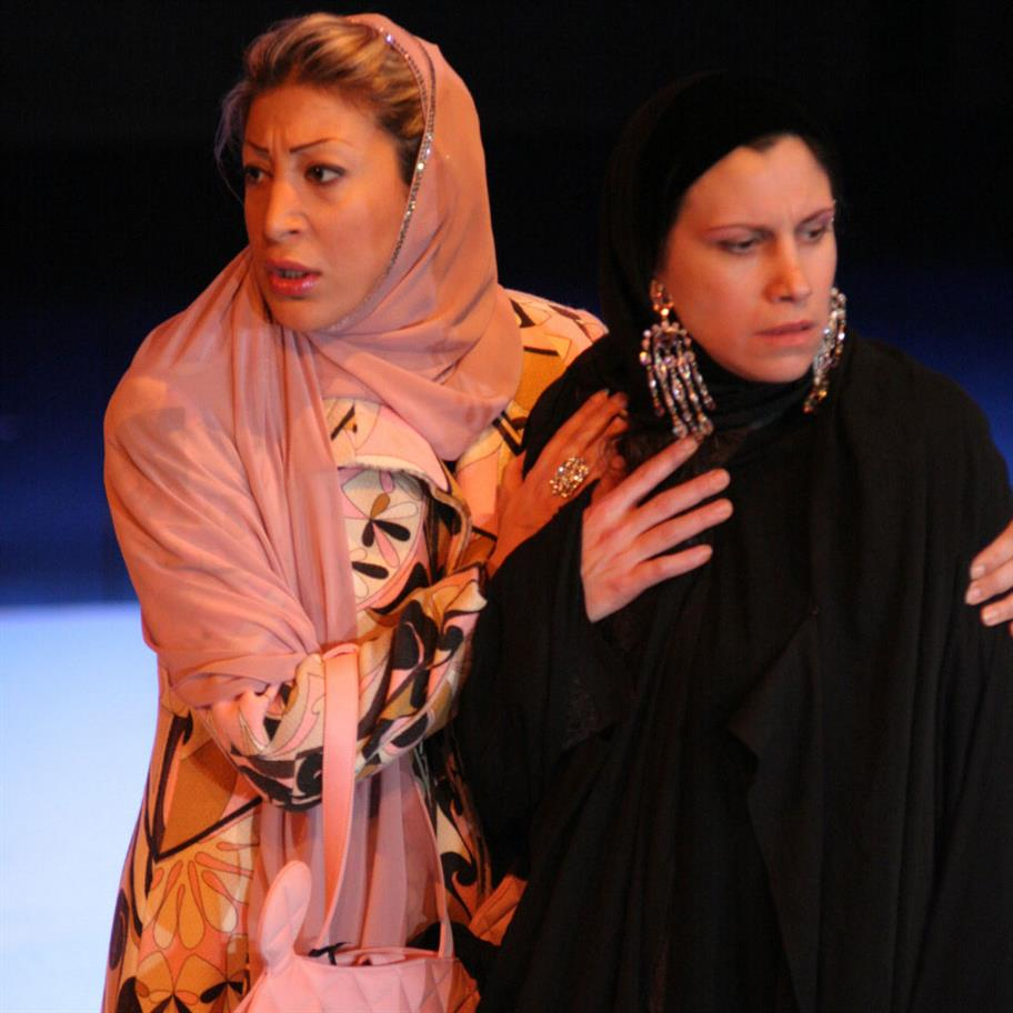 A woman in a floral dress and pink headscarf holding another woman who is in black and wearing extravagant earrings