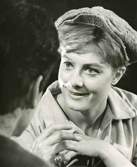 Head and shoulders photo of a young smiling woman wearing a floppy cap, looking at a young man