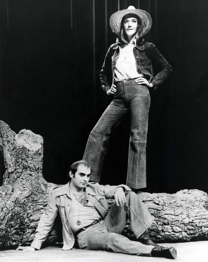 Woman in denim jeans and jacket with straw hat stands on a large tree trunk, against which a young man with open jacket and medalion sits