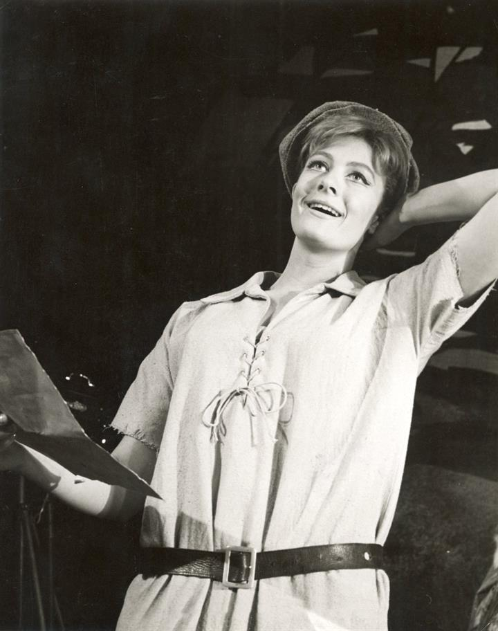 Young radiant smiling woman wearing a man's short-sleeved shirt with belt and cap holds a letter