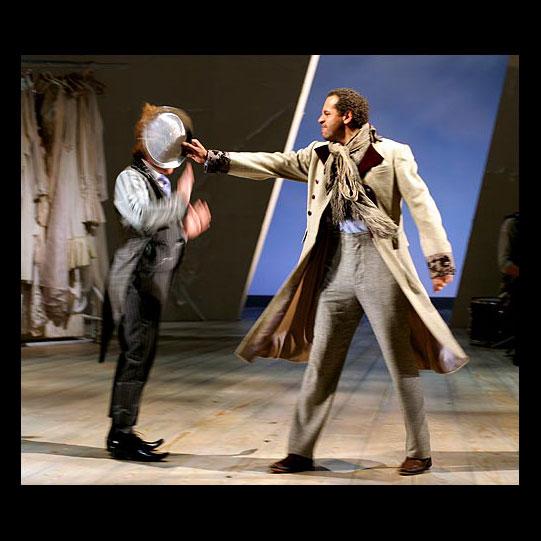 Antipholus of Syracuse (Joe Dixon, right) angrily beats Dromio of Syracuse (Jonathan Slinger).