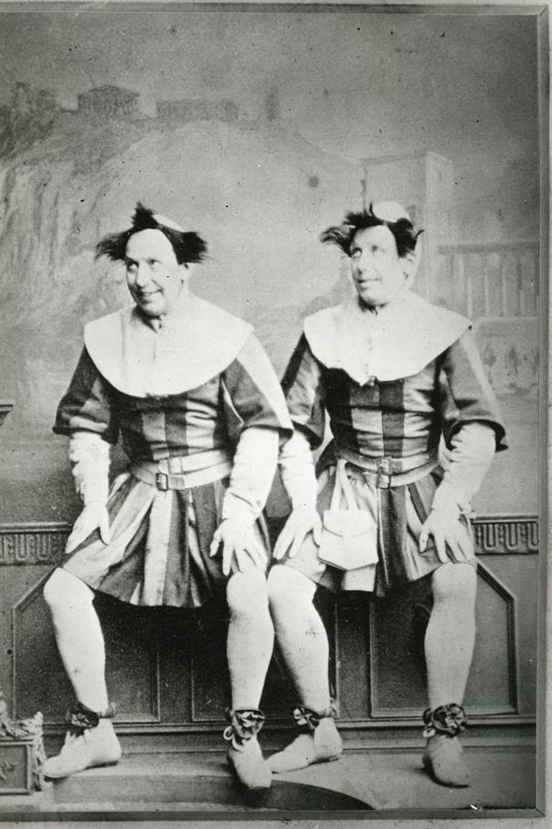 very old black and white photo of two men dressed in jesters outfits looking the same