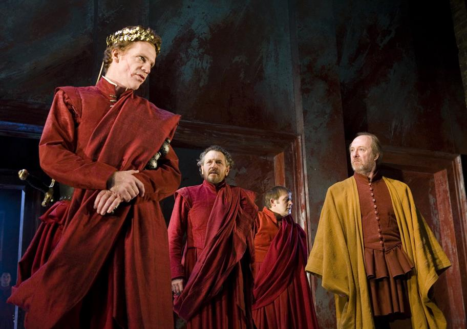 Coriolanus standing with other men, all of them wearing red togas apart from one man wearing a yellow robe
