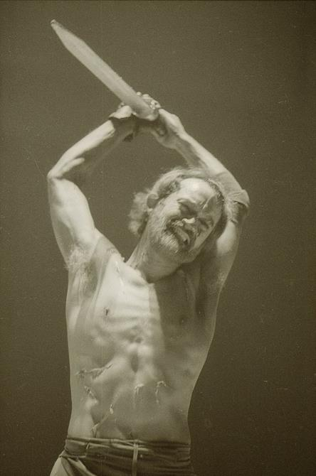 A shirtless Ian Hogg as Coriolanus raises a knife over his head