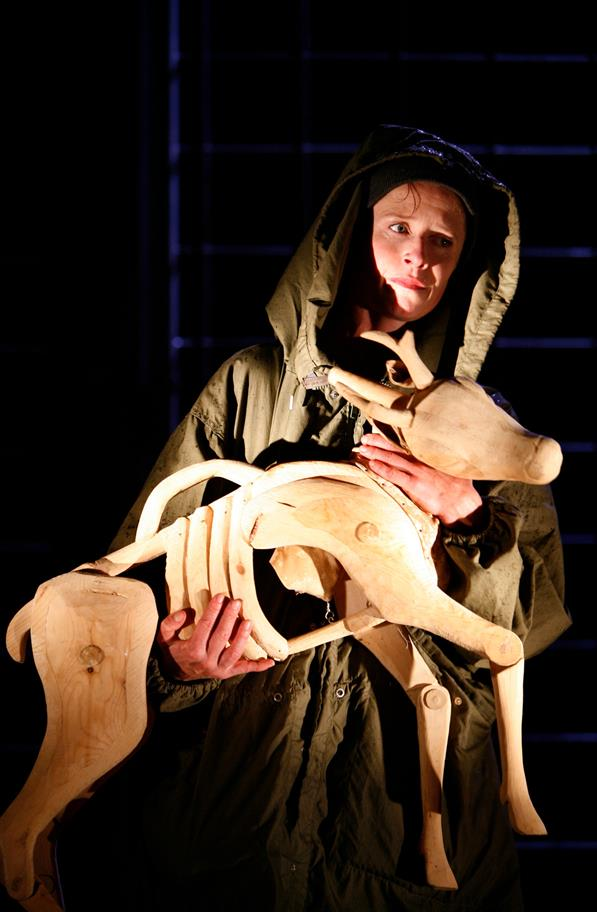 A hooded figure holding a wooden deer sculpture