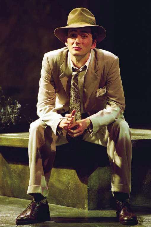 David Tennant as Antipholus of Syracuse, wearing a light coloured suit and a matching hat