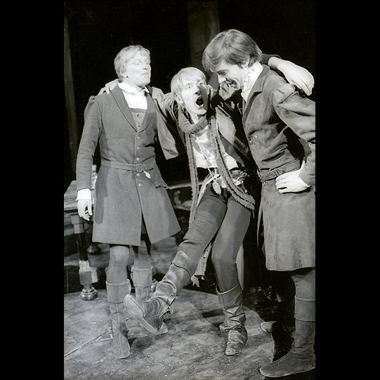 Three men talk animatedly on stage