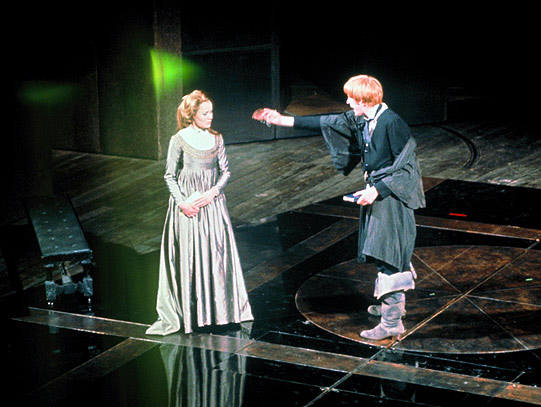 A man and woman stand on stage talking