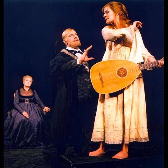 A woman stands on stage playing a guitar as others look on in despair
