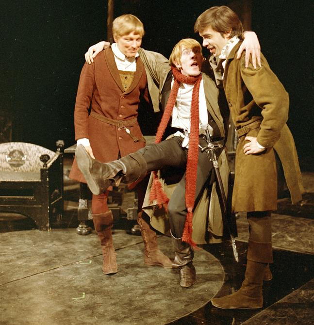 Hamlet (David Warner)  with leg in the air is supported between his two school friends, Rosencrantz and Guildenstern (Hamlet, 1965)