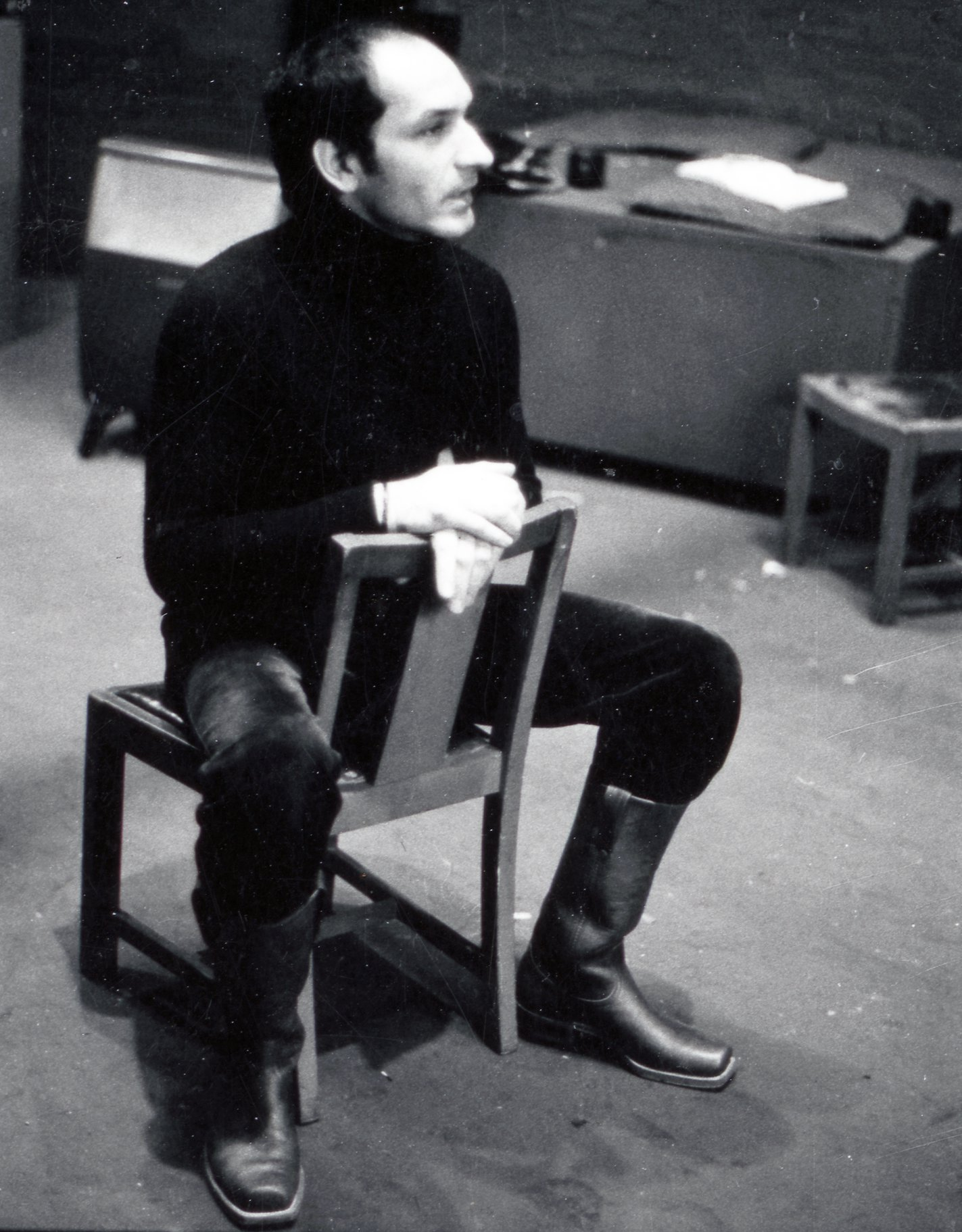 Ben Kingsley sits back to front on a chair during Hamlet rehearsals in 1975