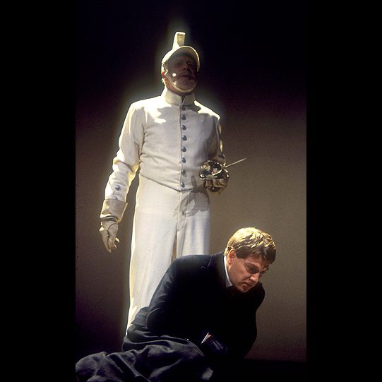 Man crouches on stage whilst another man stands dressed in white with a sword in hand