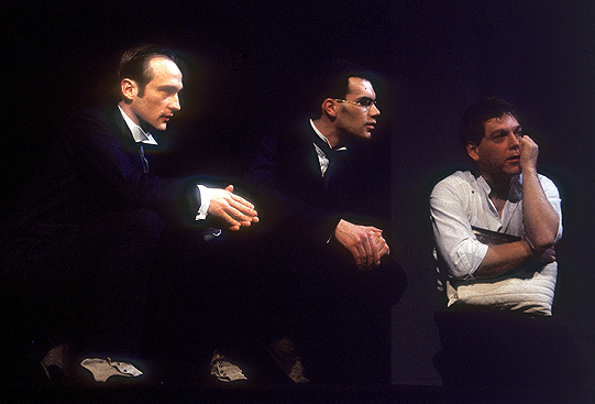 Three men sit on stage looking outwards