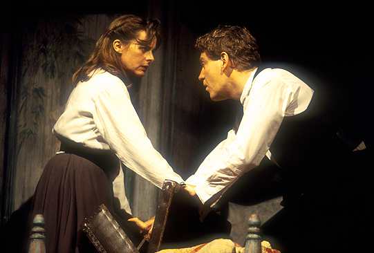 A man and woman talk on stage
