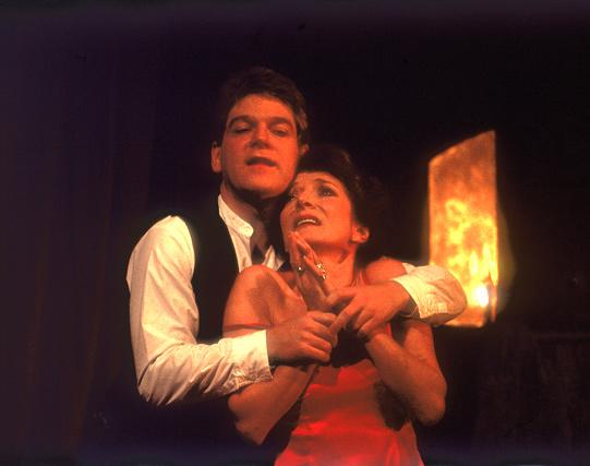 A man and woman hug on stage